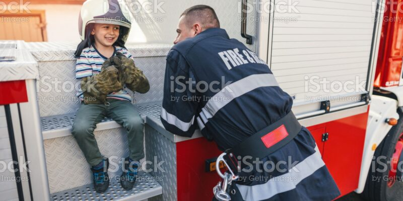 Little boy playing with firefighter helmet and gloves and talking with real firefighter